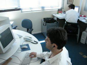 Foto com dois homens trabalhando em diferentes mesas em um escritório, com um à frente e outro ao fundo, em uma cadeira de rodas.