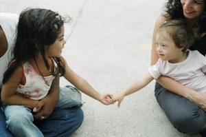 Foto de duas meninas pequenas sorrindo tocando as mãos uma da outra. A menina no lado direito tem Síndrome de Down
