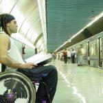 Homem branco em cadeira de rodas, com cabelo rastafári, lendo livro na estação de trem.