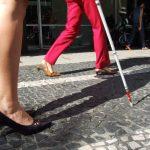 Pernas de mulher com salto alto e bengala de ponta vermelha.