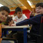 Crianças na mesa em ambiente escolar, uma delas em cadeira de rodas acenando com a mão.