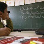 Garoto em sala de aula utiliza lente de aumento para ler atividade na lousa.