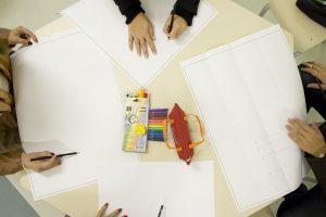 Foto de uma mesa vista de cima. Nela há papéis, uma caixa de lápis de cor e mãos adultas escrevendo nas folhas espalhadas