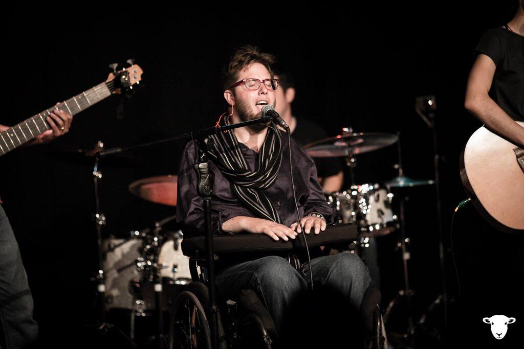 Foto de Dôdi, um homem branco de cabelos e barba louros. Ele está em uma cadeira de rodas no palco, com músicos ao fundo