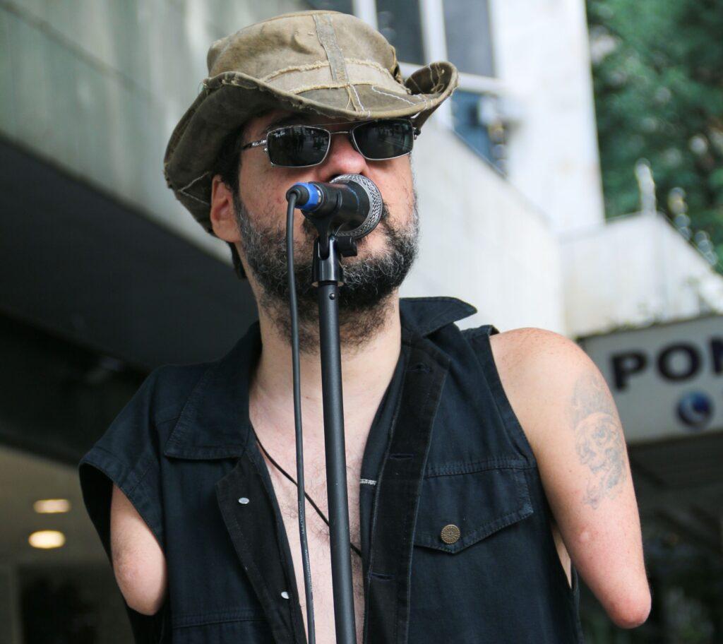 Foto de Dudé, um homem branco, com barba e cabelos castanhos, que usa óculos, chapéu e um colete. Ele tem má formação e só uma parte dos dois braços