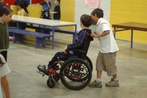 Aluno empurra a cadeira de rodas do colega em um pátio escolar com outras crianças.