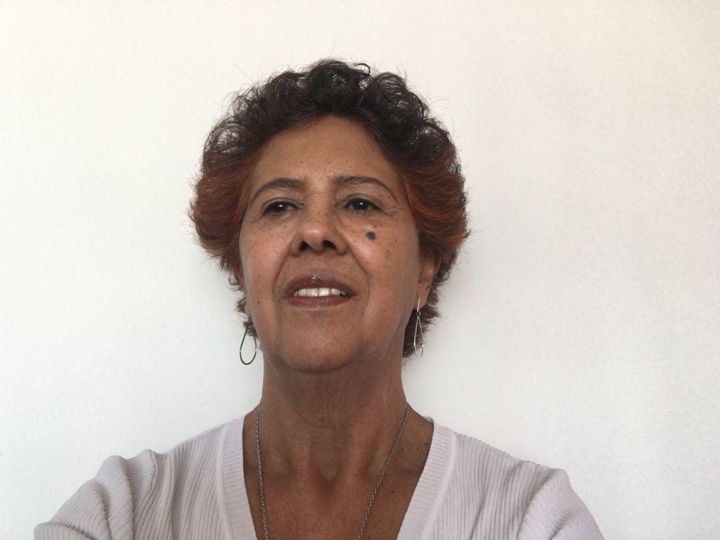 Foto de Elza Ambrosio, uma mulher negra, de cabelos curtos cacheados e em tor avermelhado. Ela olha para a direita com uma expressão contemplativa.