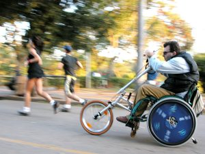 Foto de um homem cadeirante em uma bicicleta adaptada, ele está em um espaço aberto e arborizado, com pessoas praticando atividades físicas.