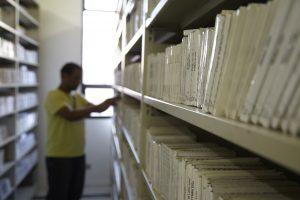 Foto das estantes da biblioteca circulante da Fundação Dorina, com diversas caixas de CDs. Ao fundo, há um homem desfocado manuseando o acervo.