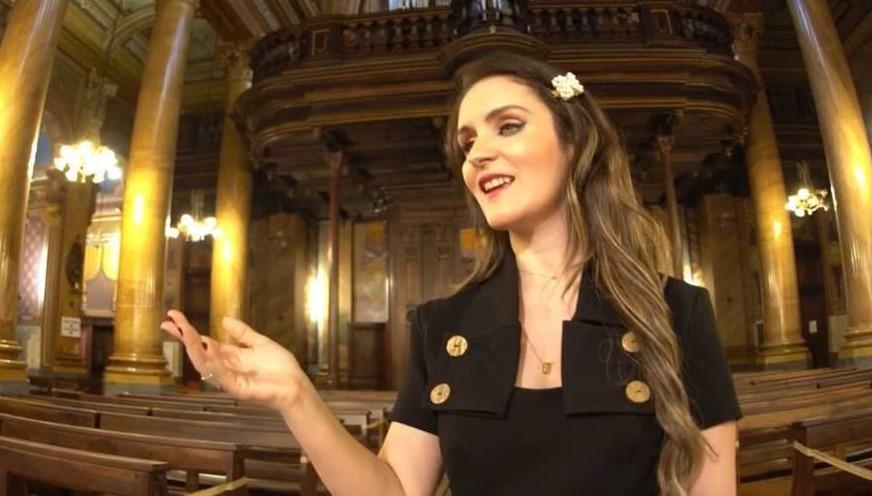 Foto de Giovanna, uma mulher branca com longos cabelos loiros. Ela está em uma sala ampla, como um teatro e tem os olhos claros, indicando cegueira.