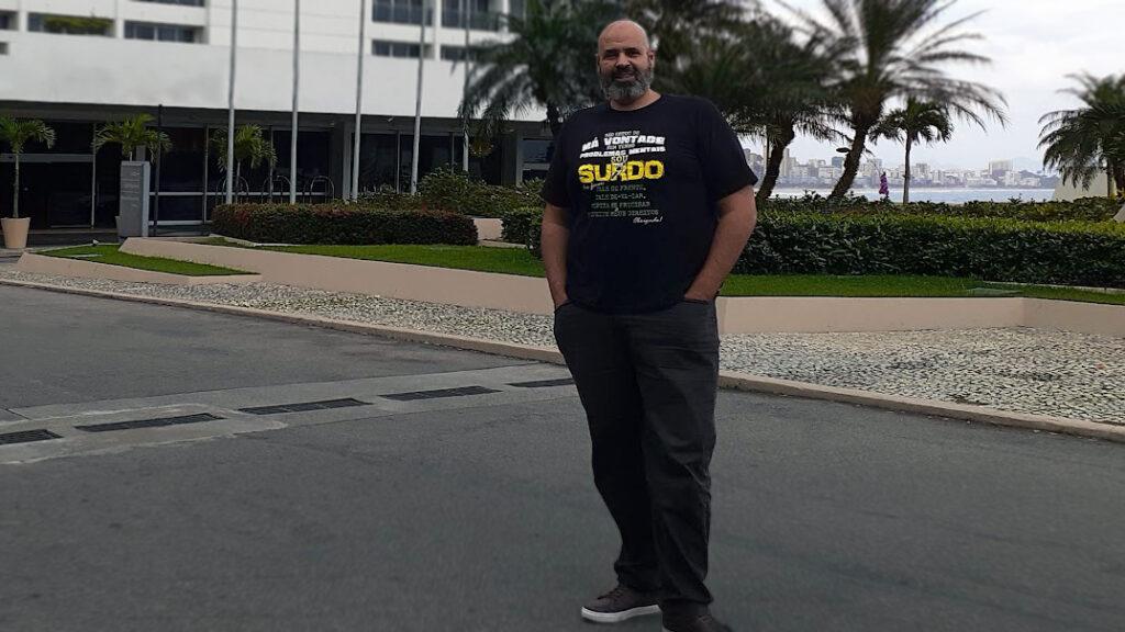 Foto de Geovane Souza, um homem negro, careca, com barba grisalha. Ele está em um ambiente aberto, com uma praia ao fundo, de pé, e olha na direção da câmera