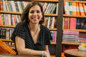 Foto de Lak Lobato, uma mulher branca, com cabelos longos e castanhos que está sorrindo e olhando na direção da câmera. Ao fundo, há estantes de livros