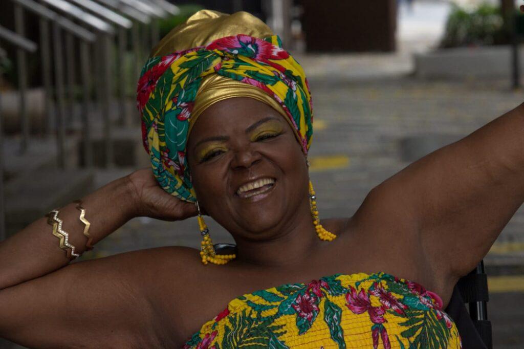 Foto de Mona, uma mulher negra, com um turbante em amarelo, verde e vermelho, com uma das mãos atrás da cabeça e sorrindo