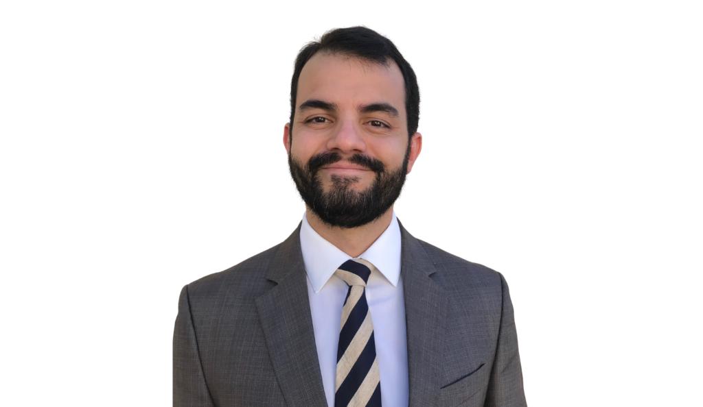 Foto de Paulo Sugai, um homem branco de cabelos e barba escurps. Ele usa um terno cinza e olha na direção da câmera, sorrindo