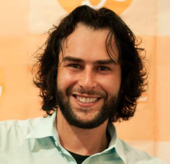 Foto de Pedro Ronan, um homem branco de cabelo longo e barba castanhos. Ele olha para a câmera e está sorrindo