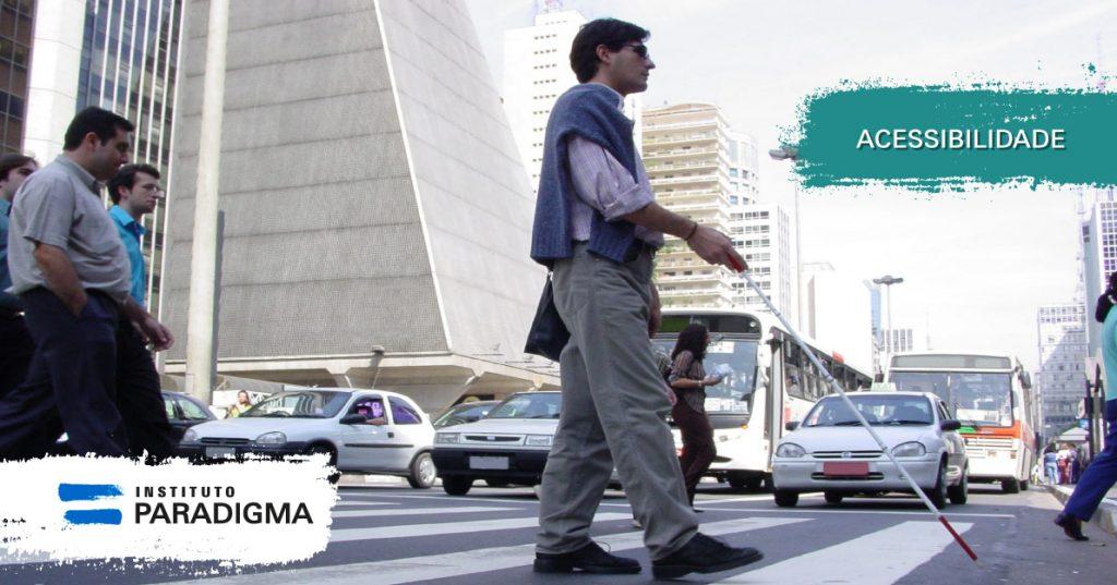 Homem surdocego com a bengala branca e vermelha, atravessando rua na faixa de pedestres. Texto: Acessibilidade.