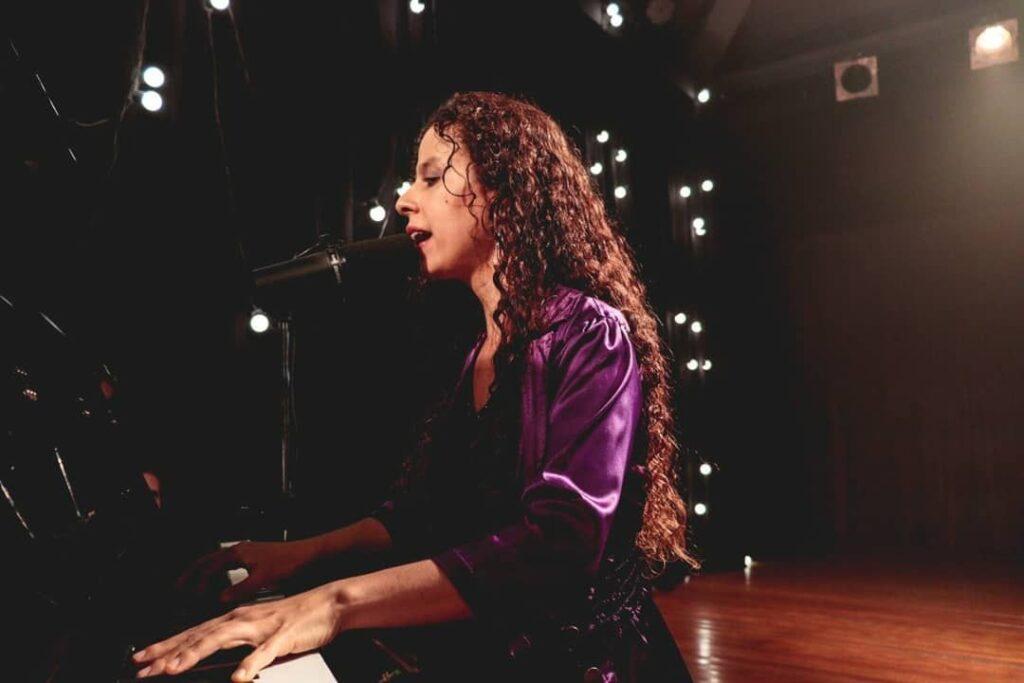 Foto de Sara, uma mulher branca, ao piano, com um microfone próximo à boca. Ela tem longos cabelos cacheados e está em um palco amplo, como um teatro