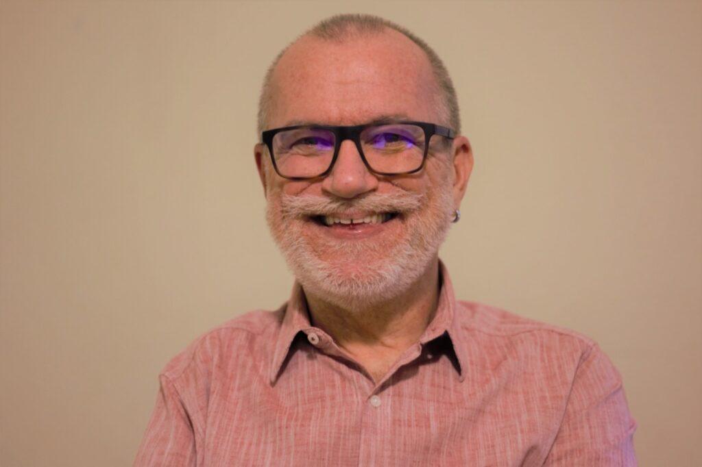 Foto de Tuca Munhoz, um homem branco, de barba branca e cabelos raspados que usa óculos com armação preta e uma camisa cor de rosa. Ele sorri e olha na direção da câmera