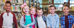Foto com um grupo de seis crianças, três meninas e três meninos, sorrindo e olhando na direção da câmera. Elas estão em uma sala com estantes de livros ao fundo