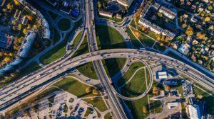 Foto aérea de pontes e estradas arredondadas que se encontram e espaços arborizados entre elas