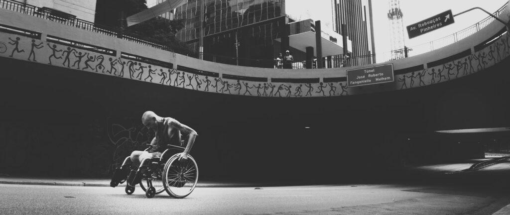 Foto em preto e branco em plano geral de um viaduto em São Paulo, com um homem cadeirante abaixo dele
