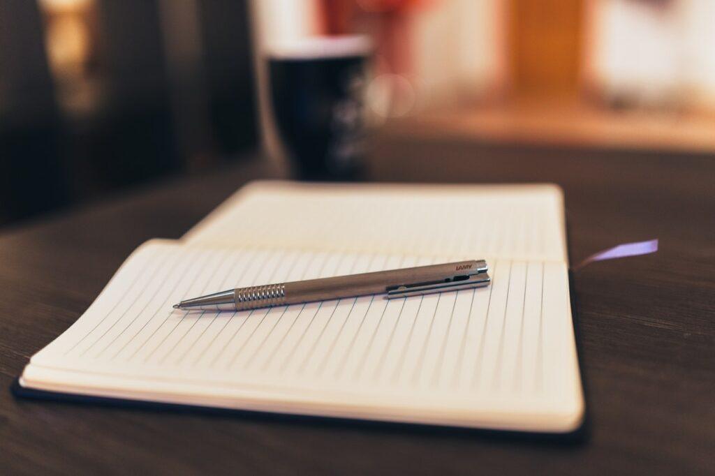 Foto de uma caderneta aberta com uma caneta apoiada sobre ela