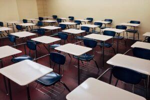 Foto de uma sala de aula vazia, com diversas carteiras enfileiradas