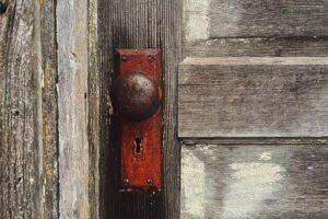 Foto em plano detalhe de uma maçaneta bola, bem antiga em uma porta de madeira